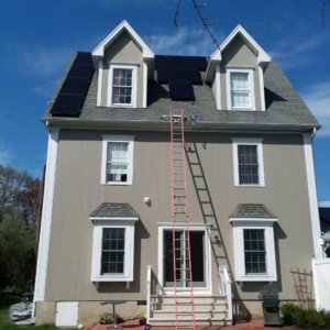 Solar panels installed on a house with a ladder in the front.