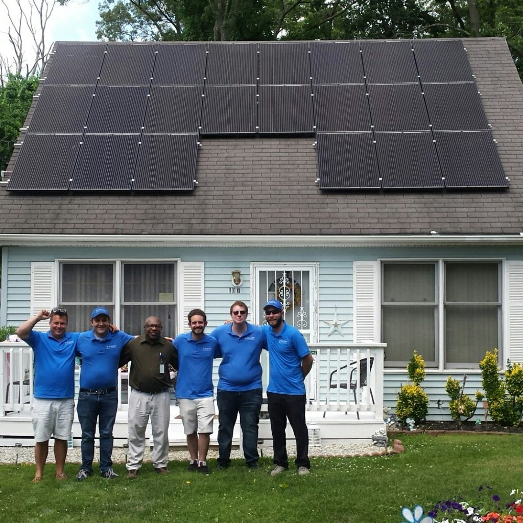 PosiGen employees posing in front of a house in New Jersey with newly installed solar panels.