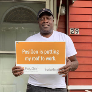 "A customer holding a sign saying ""PosiGen is putting my roof to work""."